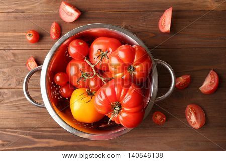 Different tomatoes in colander on wooden background