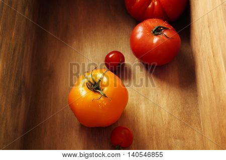 Different tomatoes with water drops in wooden box