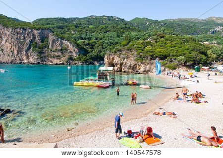 CORFU-AUGUST 26: Palaiokastritsa beach holidaymakers sunbathe on the beach on August 262014 on the Corfu island Greece. Palaiokastritsa is a village with famous beaches in the North West of Corfu.