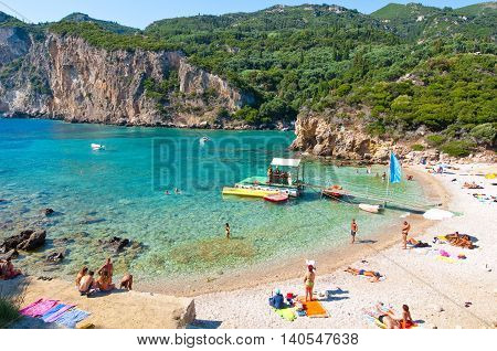CORFU-AUGUST 26: One of the Palaiokastritsa beach people sunbathe on the beach on August 262014 Corfu island Greece. Palaiokastritsa is a village with famous beaches in the North West of Corfu.