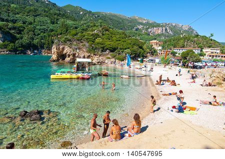 CORFU-AUGUST 26: Palaiokastritsa beach tourists sunbathe on the beach on August 262014 on the island of Corfu Greece. Palaiokastritsa is a village with famous beaches in the North West of Corfu.