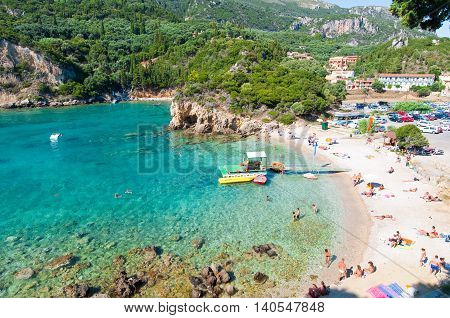 CORFU-AUGUST 26: Palaiokastritsa people sunbathe on the beach on August 262014 Corfu island Greece. Palaiokastritsa is a village with famous beaches in the North West of Corfu.
