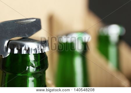 Bottles in paper beer package with opener, closeup