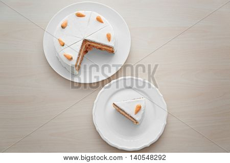Sliced carrot cake with slice on wooden table, top view