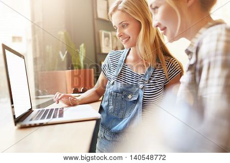 Young Students Watching Video Online From Modern Laptop With Wi-fi In Stylish Café. Blond Girls Dres