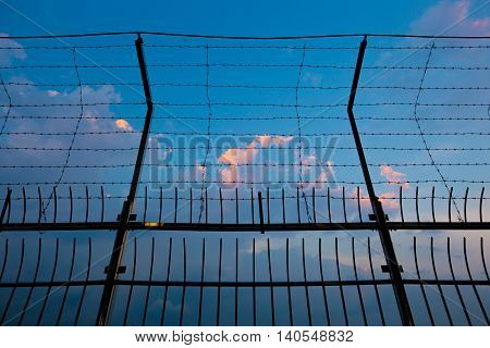 Barbed wire fence silhouettes against cloudy dark blue sky at sunset