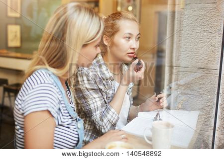Portrait Of Two Women In Casual Clothes Sitting In A Café. Female Friends Applying Lipstick Properly