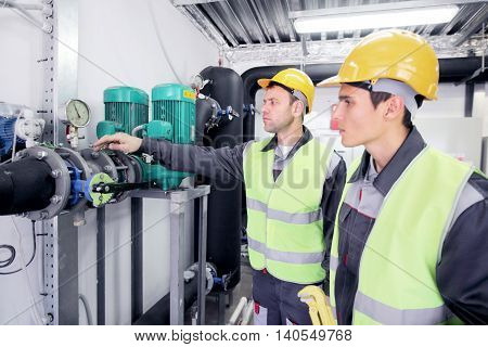 Two workers in hardhats at plant checking parameters of pressure