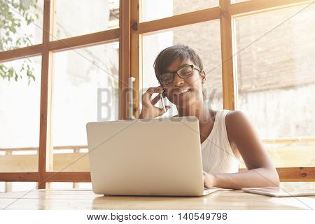 Beautiful Young Freelancer Talking On Phone With Her Clients. Dark-skinned Girl In Glasses With Brun