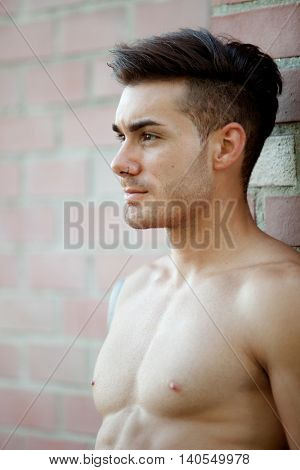 Handsome fit athletic shirtless young man with piercing on his nose