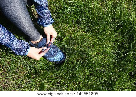 Woman tying shoelace on grass in a park