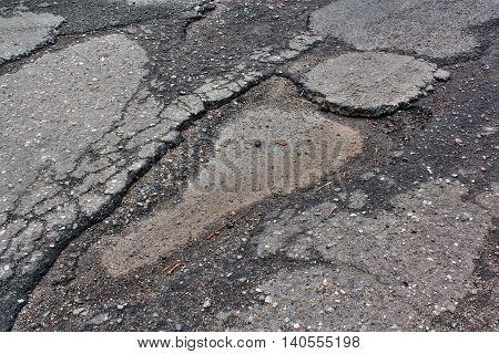 A large hole in the pavement asphalt gap