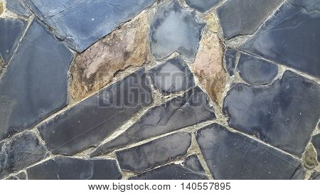 gray and brown, smooth and rough, quadrilateral shapes seen in stone vaneer siding, concrete wall in Songkhla, Thailand