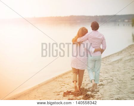 Toned picture of happy couple in love walking along caribbean beach in evening. Beautiful mature people hugging and communicating about life.