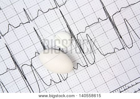 Electrocardiogram ECG and white pills medical  vitamin