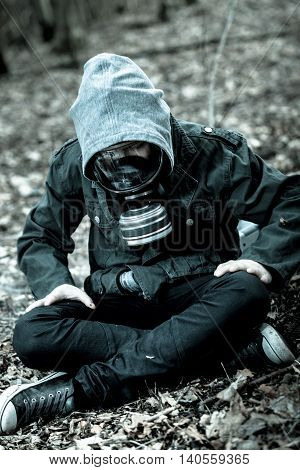 Tense Child In Gas Mask Sitting On Ground