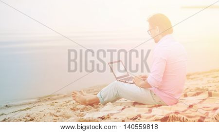 Toned picture of handsome mature freelancer working on laptop computer. Author in glasses writing poem at beach. He is becoming inspired by beautiful sea.
