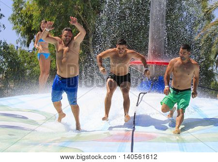 Rhodes Greece-July 24 2016:Cheerful group of young people jumping on the wet bubble in the water park .Wet bubble is one of many popular game for adults and children in Water park..Water Park is located on the island of Rhodes in Greece