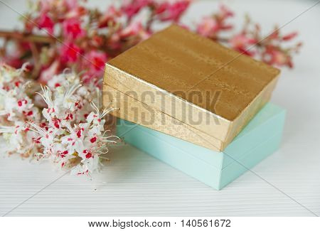There Gold and Blue Boxes with White and Pink  Branches of Chestnut Tree are on White Table,Selective Focus,Back View