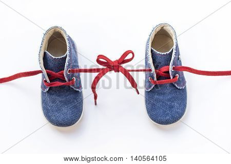 Baby shoes tied together isolated on white background. Top view.