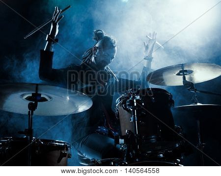 Silhouette of the drummer on stage. Dark background, smoke, spotlights