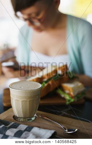 Concept of breakfast with coffee and sandwiches. Girl on background reading the news in your smartphone raf coffee in the foreground.