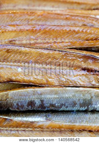 Stack of smoked fish close up background
