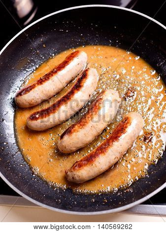 Cooking sausages in the dripping pan with oil