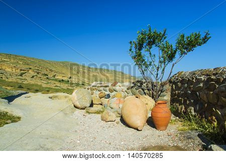 Ceramic ancient amphora for wine on a background of mountains outdoors