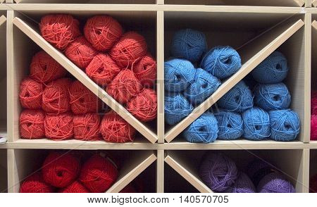 many colored threads laid out in the shelf