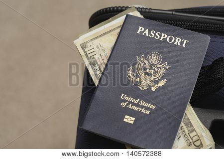 a passport with money on a suitcase