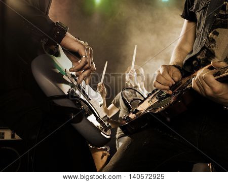 Rock band performs on stage. Bassist in the foreground. Close-up.
