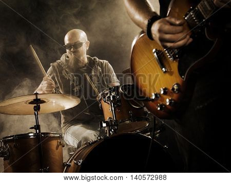 Rock band performs on stage. Guitarist bass guitar and drums. The guitarist plays solo.
