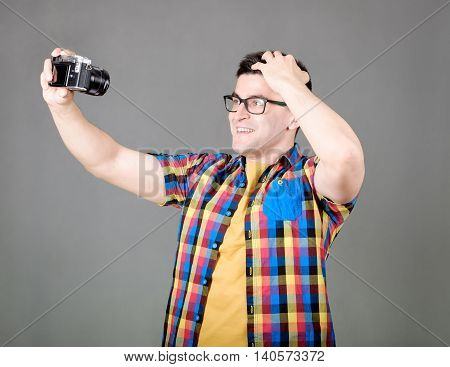Handsome man dressed in a multicolored shirt with taking selfie with photo camera isolated on gray background
