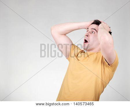 Amazed man looking left isolated on gray background
