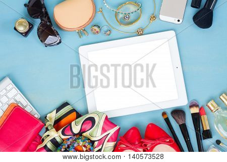 styled feminine desktop - woman fashion items on blue wooden background, copy space on tablet screen