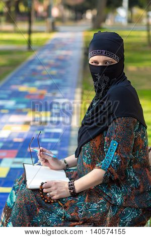 Portrait of intellectual Eastern Woman in traditional clothing sitting in Park reading Book looking at camera