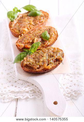 Aubergine spread over brown bread on board