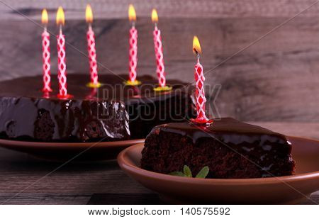 Chocolate cake slice with chocolate glaze and with candle