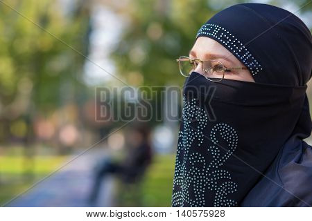 Portrait of intellectual Eastern Woman in traditional clothing sitting in Park with glasses looking aside