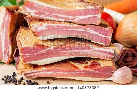 Stack of smoked pork ribs with dry red beans and vegetables on a wooden board