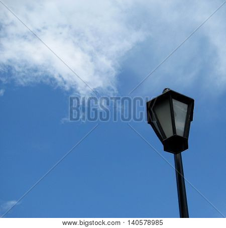 Classic black and white outside street lantern against blue sky background