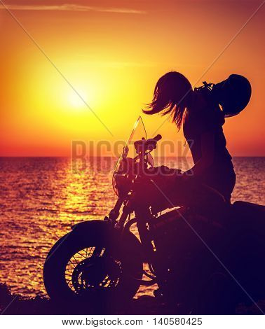 Silhouette of a biker woman on the beach over sunset background, enjoying life on the motorcycle, bikers tour, freedom concept