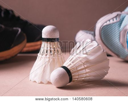 sports set of black orange sport shoes and blue sport shoe and shuttlecocks with two badminton racket on sport background with selective focus
