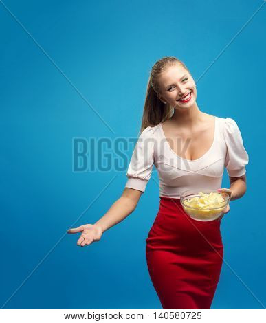 Portrait of fashionable young blond woman in pink-red dress, bright make-up holding, eating fried potato, chips and  over blue background. Copy-space. Unhealthy eating. Junk food concept.