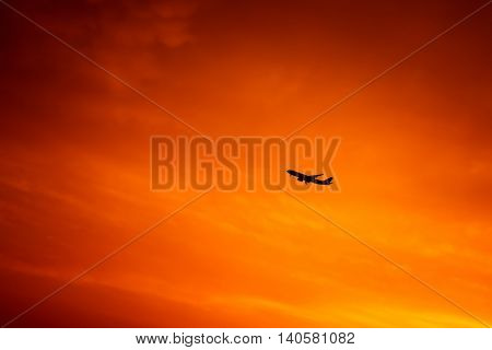 Airplane in the sky, silhouette of aircraft over bright orange sunset background, expensive lifestyle, transportation concept