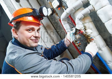 Plumber technician works with water valve