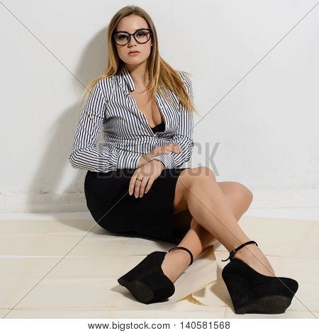 Beautiful business fatigue woman in a striped shirt black skirt and shoes sitting on the floor on paper
