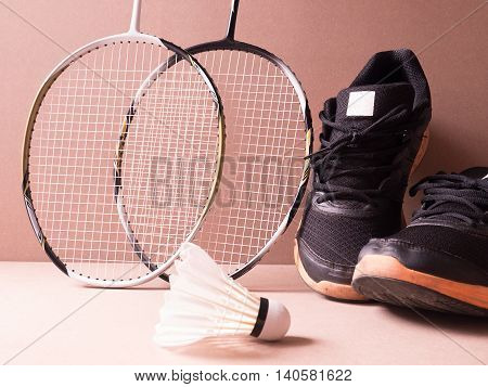 sports set of black orange sport shoes and shuttlecocks with two badminton racket on sport background in concept family activity