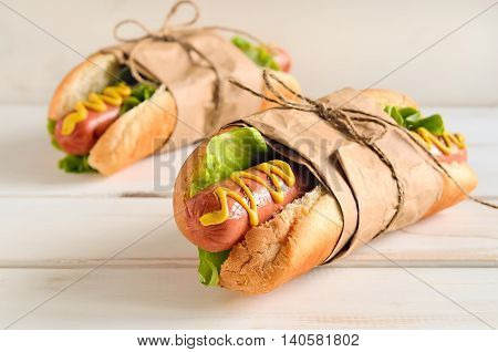 Two hot dogs with american yellow mustard and fresh lettuce rolled in a paper and knotted with bow on a light wooden background. Good as a present for Hot Dog celebration day. Close up.